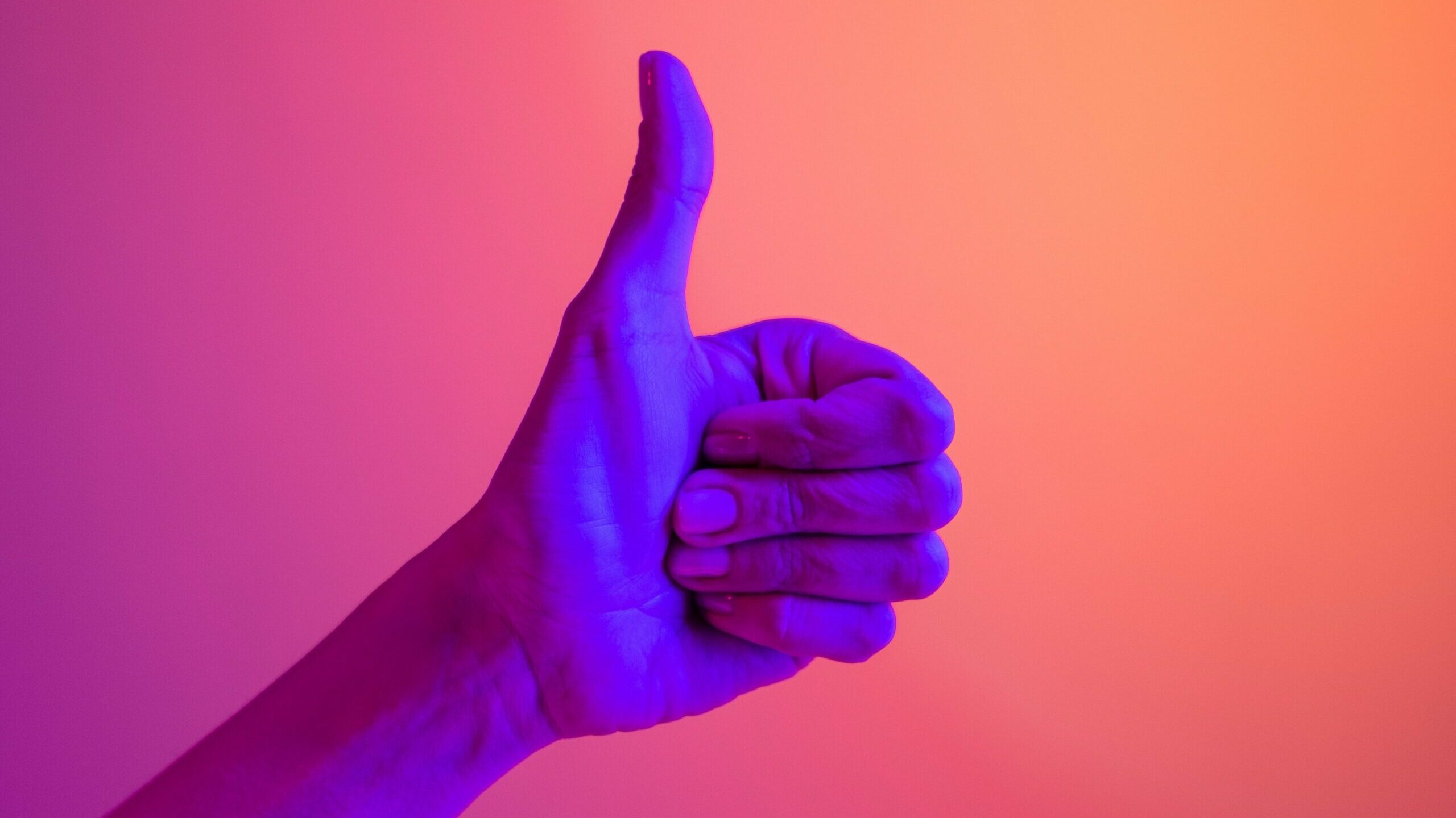 A hand lit bright purple against a pink and orange background, showing the thumbs up sign.